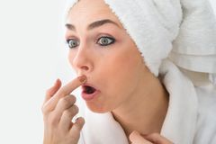 Donna colpita che esamina brufolo sul fronte Fotografia Stock Libera da Diritti