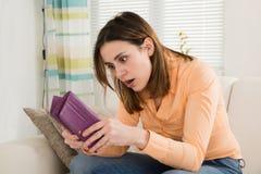 Donna colpita che esamina la sua borsa Immagini Stock