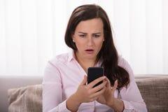 Donna colpita che esamina telefono cellulare immagini stock libere da diritti
