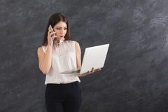 Donna colpita che parla sul telefono e che tiene computer portatile Fotografia Stock Libera da Diritti