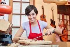 Donna come apprendista del creatore della chitarra Immagini Stock