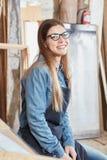 Donna come contenuto sorridente dell'apprendista del carpentiere Immagine Stock