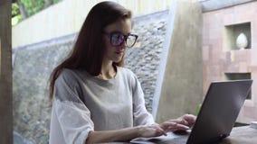 Donna in computer portatile di uso di vetro Donna di affari che lavora al computer durante la vacanza Immagini Stock Libere da Diritti