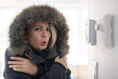 Donna con abbigliamento caldo che ritiene il freddo dentro la Camera fotografie stock libere da diritti