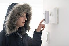 Donna con abbigliamento caldo che ritiene il freddo dentro la Camera immagine stock libera da diritti