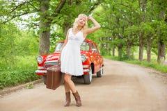 Donna con aiuto aspettante della valigia Fotografie Stock Libere da Diritti