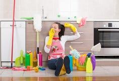 Donna con attrezzature per la pulizia e prodotti sul pavimento della cucina Immagini Stock