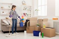 Donna con attrezzature per la pulizia pronte a stanza pulita immagini stock