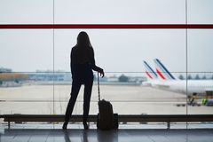 Donna con bagaglio a mano in aeroporto internazionale, osservante attraverso la finestra gli aerei immagini stock