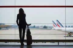 Donna con bagaglio a mano in aeroporto internazionale, osservante attraverso la finestra gli aerei immagine stock