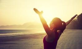 Donna con a braccia aperte sopra la spiaggia di alba Immagine Stock