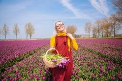 Donna con capelli biondi che portano un vestito rosso e una blusa gialla che tengono un canestro con i fiori dei tulipani fotografie stock