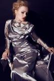 Donna con capelli biondi e trucco luminoso che portano vestito d'argento lussuoso Fotografia Stock