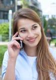 Donna con capelli biondi lunghi che flirtano al telefono fuori Fotografia Stock