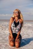 Donna con capelli biondi in vestito di nuoto elegante che posa vicino immagini stock