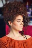Donna con capelli ricci lunghi alzati allo studio dei capelli Fotografia Stock Libera da Diritti