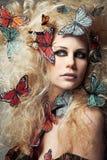 Donna con capelli ricci lunghi con le farfalle. Fotografie Stock Libere da Diritti