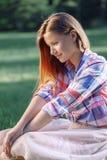 Donna con capelli rossi lunghi in camicia di plaid e gonna rosa di Tulle del tutu, sedentesi sull'erba Immagini Stock Libere da Diritti