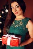 Donna con capelli scuri lunghi in vestito da verde del pizzo che tiene una scatola con un regalo Immagine Stock
