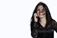 Donna con capelli sudici sul telefono, colpo dello studio Fotografie Stock
