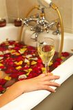 Donna con champagne ed i petali di rosa Fotografie Stock