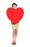 Donna con cuore enorme fatto di carta rossa Fotografia Stock