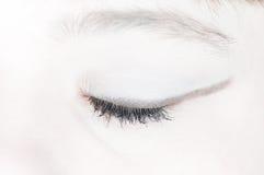 Donna con dell'occhio la parte posteriore chiusa ed il bianco dentro Fotografie Stock Libere da Diritti