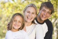 Donna con due bambini in giovane età all'aperto che sorridono Fotografia Stock Libera da Diritti