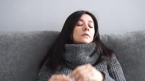 Donna con febbre e naso semiliquido facendo uso di un fazzoletto stock footage