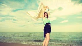 Donna con funzionamento dello scialle sulla spiaggia Fotografia Stock