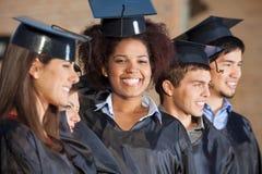 Donna con gli amici sul giorno di laurea all'istituto universitario Fotografia Stock Libera da Diritti