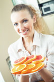 Donna con gli aranci ed i pompelmi Immagini Stock