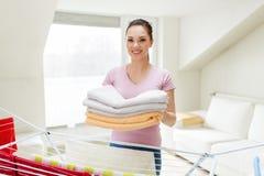 Donna con gli asciugamani e lo stendipanni di bagno a casa Fotografie Stock