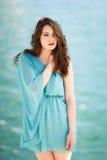 Donna con gli occhi azzurri che portano vestito blu nella spiaggia immagine stock