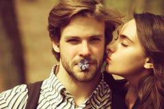 Donna con gli occhi chiusi che bacia uomo bello sulla guancia fotografia stock