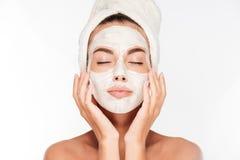 Donna con gli occhi chiusi e maschera facciale bianca sul fronte Fotografia Stock