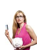 Donna con gli occhiali che tengono la carta di credito ed il porcellino salvadanaio fotografia stock libera da diritti