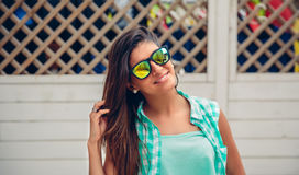 Donna con gli occhiali da sole che esaminano macchina fotografica sopra il recinto del giardino Fotografie Stock