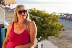 Donna con gli occhiali da sole che stanno sul balcone presto nel Morni immagini stock