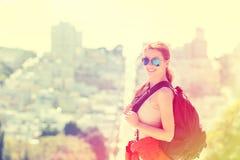 Donna con gli occhiali da sole dello zaino che viaggiano nella città di San Francisco immagini stock
