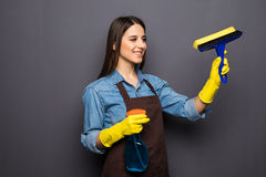 Donna con gli strumenti di pulizia della casa per la pulizia delle finestre isolate su grey Fotografia Stock