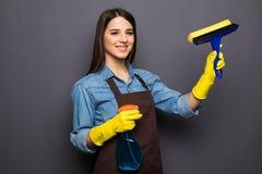 Donna con gli strumenti di pulizia della casa per la pulizia delle finestre isolate su grey Immagine Stock Libera da Diritti