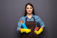 Donna con gli strumenti di pulizia della casa su grey Fotografia Stock