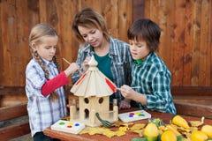 Donna con i bambini che dipingono la preparazione di casa dell'uccello per l'inverno Immagine Stock