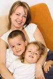 Donna con i bambini sul sofà Fotografia Stock