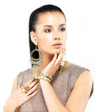 Donna con i chiodi dorati ed i bei gioielli dell'oro Fotografie Stock