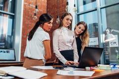 Donna con i colleghi del computer portatile che stanno nell'ufficio fotografia stock