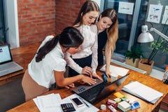 Donna con i colleghi del computer portatile che stanno nell'ufficio immagini stock