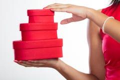 Donna con i contenitori di regalo a forma di del cuore rosso Fotografie Stock