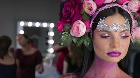 Donna con i fiori ed il trucco luminoso stock footage